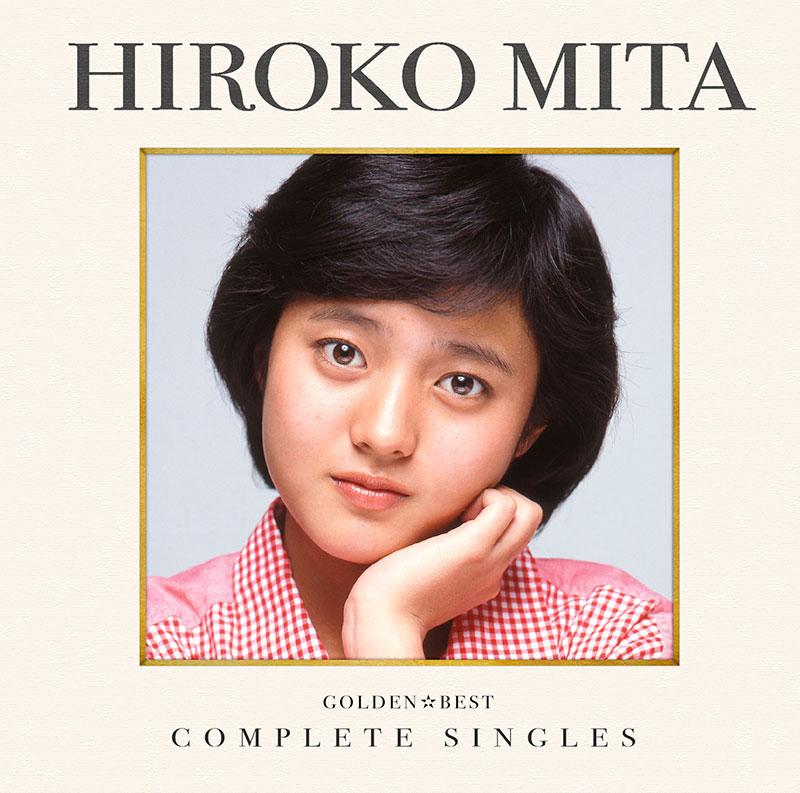 赤いギンガムチェックのシャツで頬に手を当て微笑むアイドル時代の三田寛子